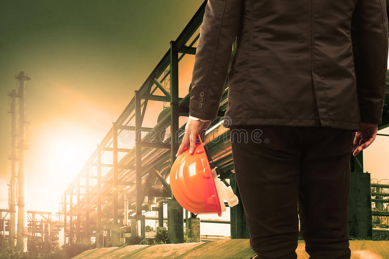Engineering man and safety helmet standing against beautiful light sun shine in heavey petrochemical industry estate royalty free stock photography