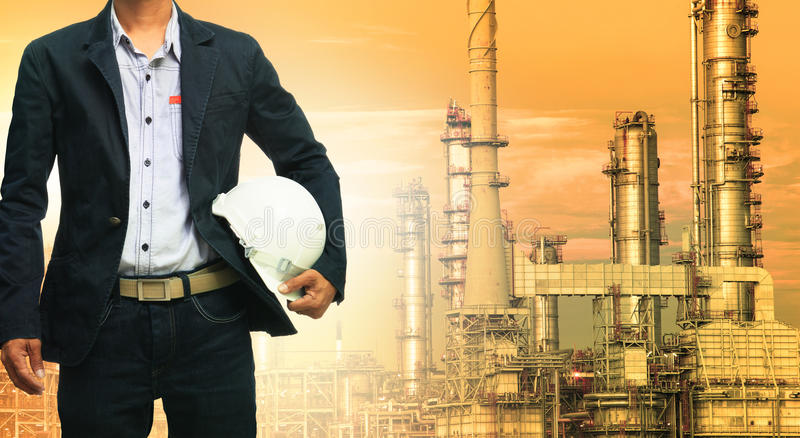 Engineering man and safety helmet standing against oil refinery stock image