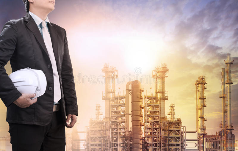 Engineering man with safety helmet standing against oil refinery royalty free stock photo