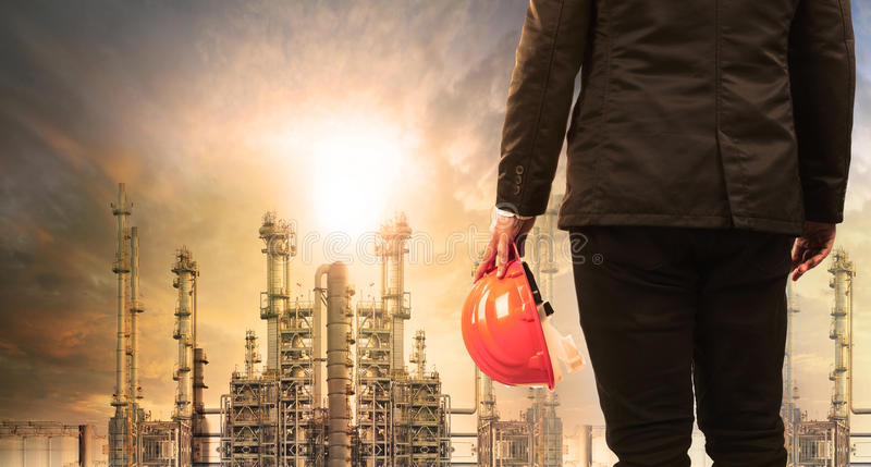 Engineering man with safety helmet standing in industry estate a. Gainst sun rising above oil refinery plant stock photo