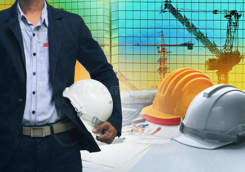 engineering man standing with white safety helmet against building and crane construction working table office use for royalty free stock photos