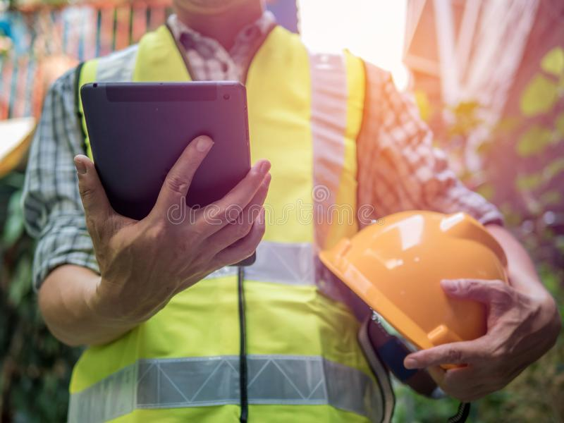 Engineering man standing with yellow safety helmet and holding tablet, work concept.  royalty free stock image