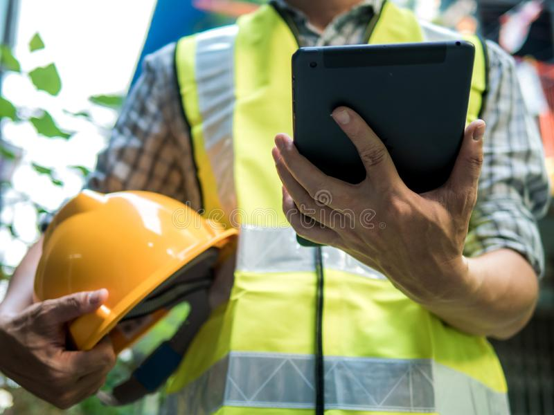 Engineering man standing with yellow safety helmet and holding tablet, work concept.  stock photos