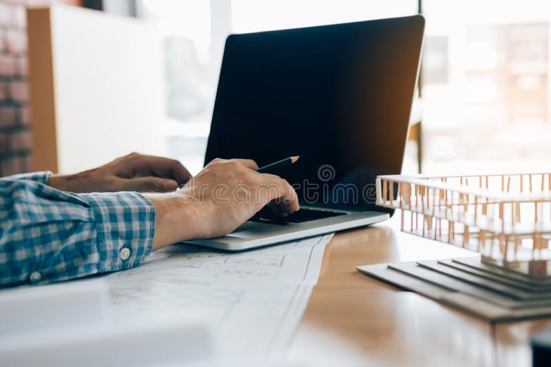 Engineering man using laptop and sitting in modern office working blueprint project stock photo