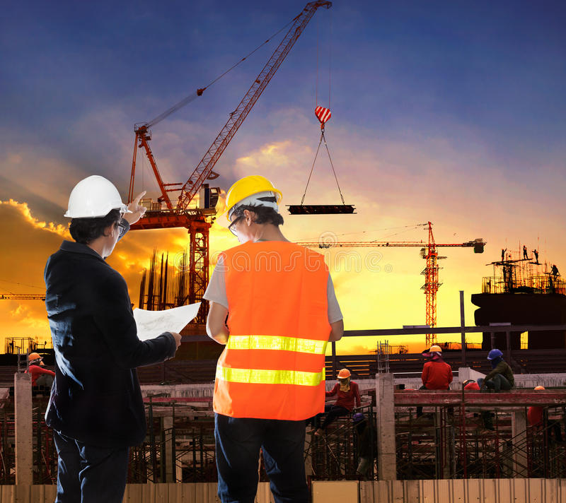 Engineering man working in building construction site with worker foreman against beautiful dusky sky royalty free stock photo