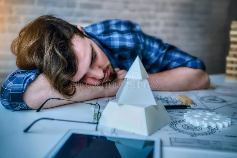 Engineering man working overwork and sleep on the desk with blueprint mechanical parts in office. having a bad stress and overwork. Time concept - Image stock image
