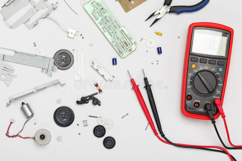 Engineering mess. Background with multimeter, electrical and mechanical parts. View above royalty free stock images