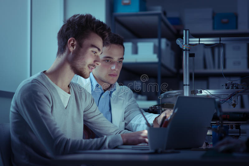Engineering students in the lab at night. They are using a laptop and working, 3D printer in the background royalty free stock images