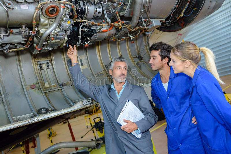 Engineering teacher checking airplane engines with students stock photos