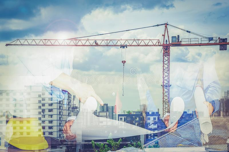 Engineering team with architects and crane lifts into the background. This is a double exposure image.  royalty free stock photography