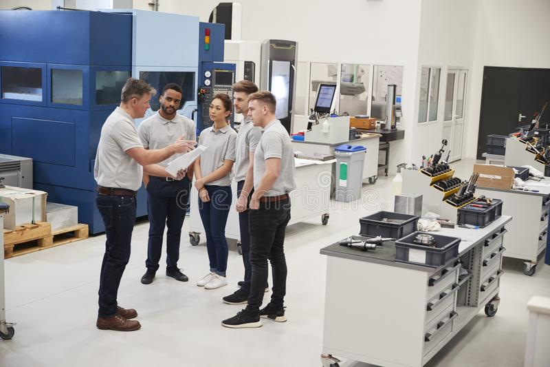 Engineering Team Meeting On Factory Floor Of Busy Workshop stock photos