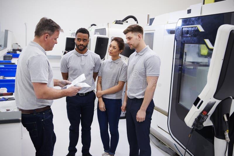 Engineering Team Meeting On Factory Floor Of Busy Workshop royalty free stock image