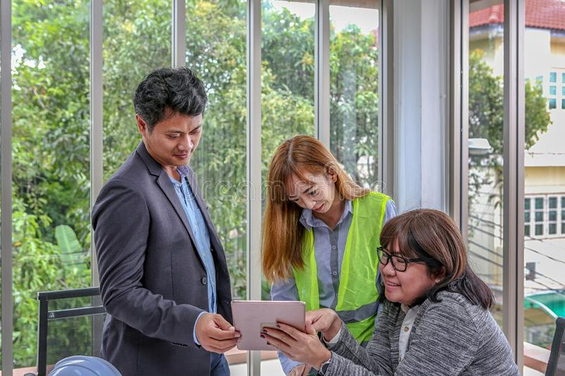 The engineering team is planning an event with joy. Group engineers discussing work in meeting room at the office. Asian people royalty free stock image