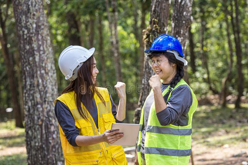 The engineering team is proud of its success. Young Engineer female holding tablet on hand. Engineer team working on project at. The forest. Electricians royalty free stock image