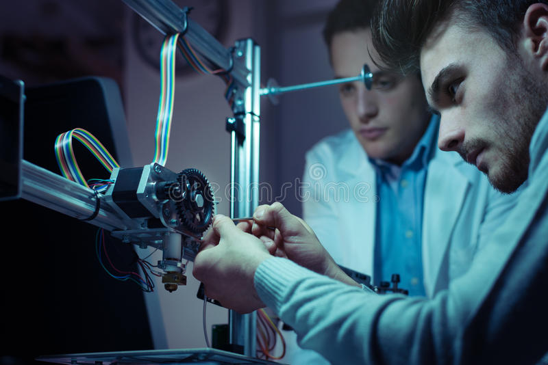 Engineering team working on a 3D printer stock photos
