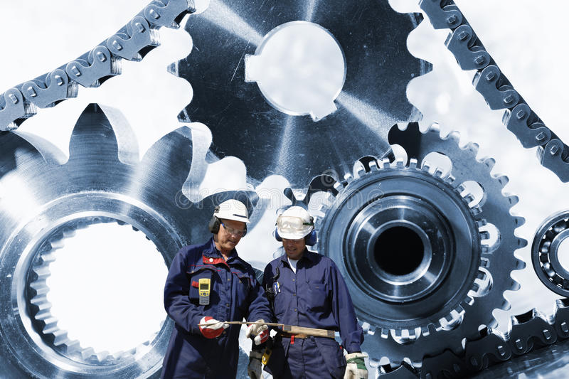 Engineering and technology. Two engineers talking with a large gears and cog machinery in background, powered by timing-chain royalty free stock image