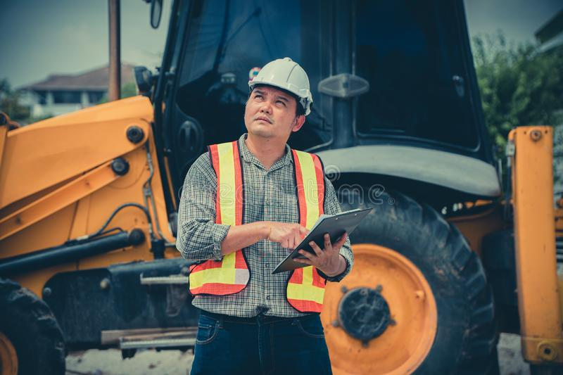 Engineering wearing a white safety helmet standing in front of the backhoe Looking at home construction work And use the tablet to stock image