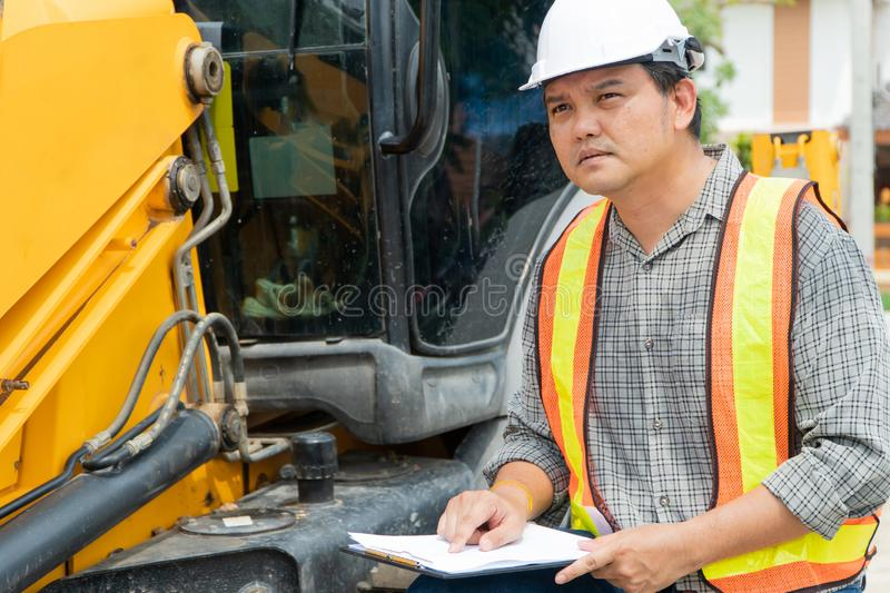 Engineering wearing a white safety helmet standing in front of the backhoe Looking at home construction work And use the tablet to. Check the blueprint with royalty free stock photos