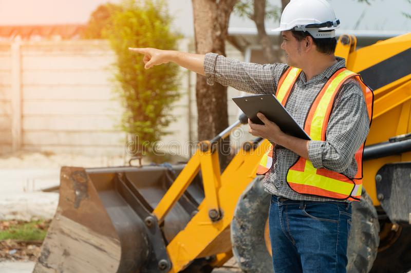 Engineering wearing a white safety helmet standing in front of the backhoe Looking at home construction work And use the tablet to. Check the blueprint with stock photos