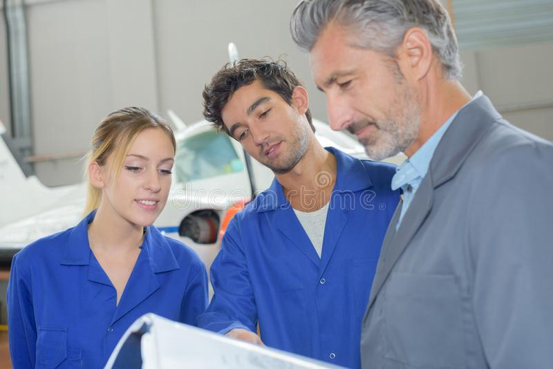 Engineers in aircraft hangar royalty free stock photo