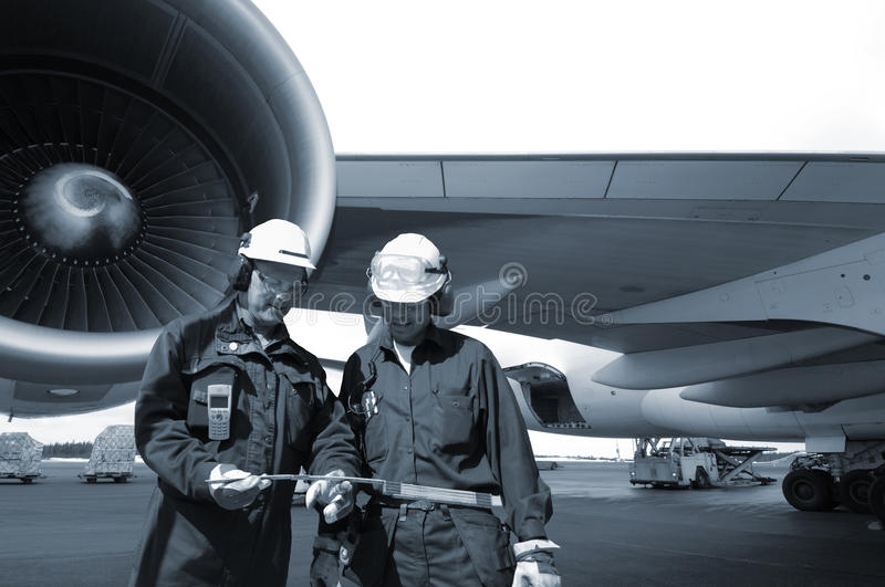 Engineers and airliner. Two air mechanics with large airliner in background, jumbo-jet, blue toning idea royalty free stock photo