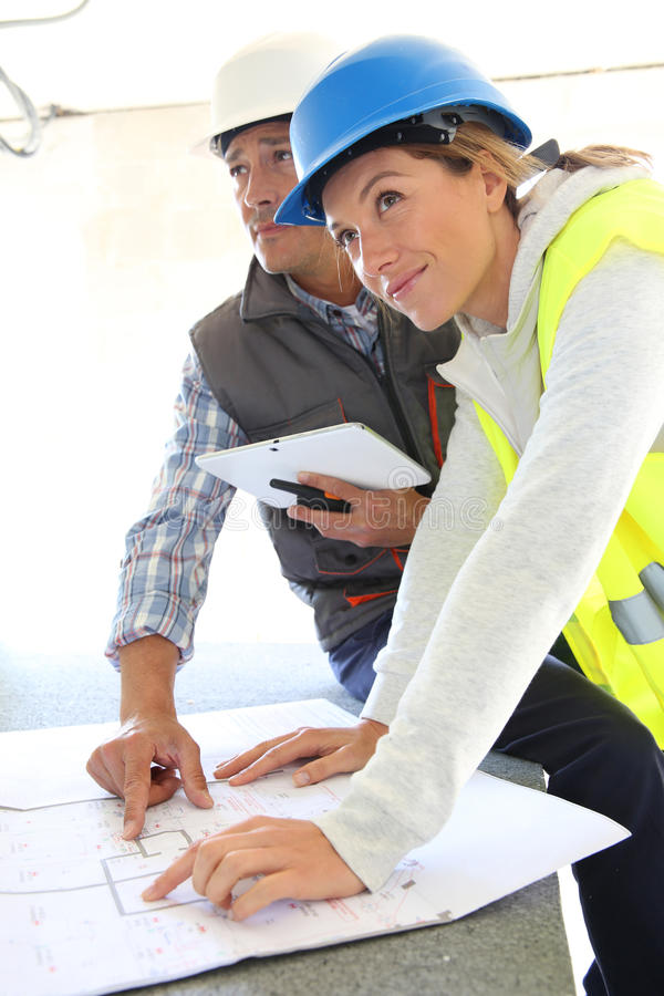 Engineers on building site using tablet royalty free stock photo
