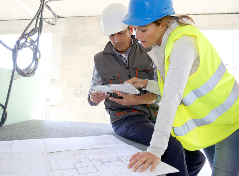 Engineers on construction site checking installations royalty free stock image