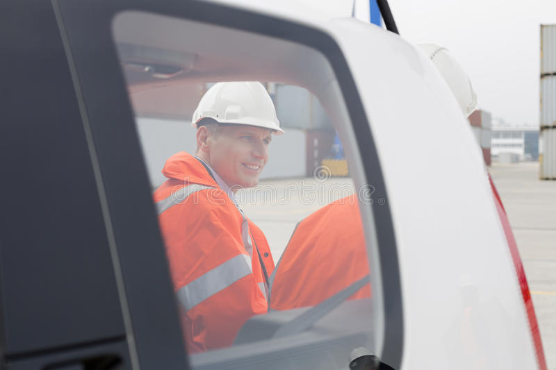 Engineers conversing beside car in shipping yard stock photography