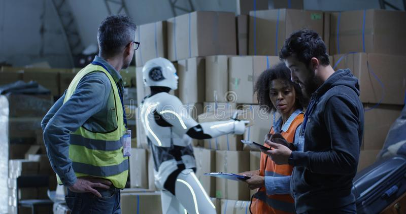 Engineers evaluating a robots work. Medium long shot of engineers evaluating a robots work in a warehouse stock image