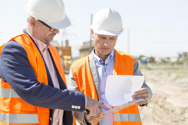 Engineers examining documents on clipboard at construction site against clear sky stock images