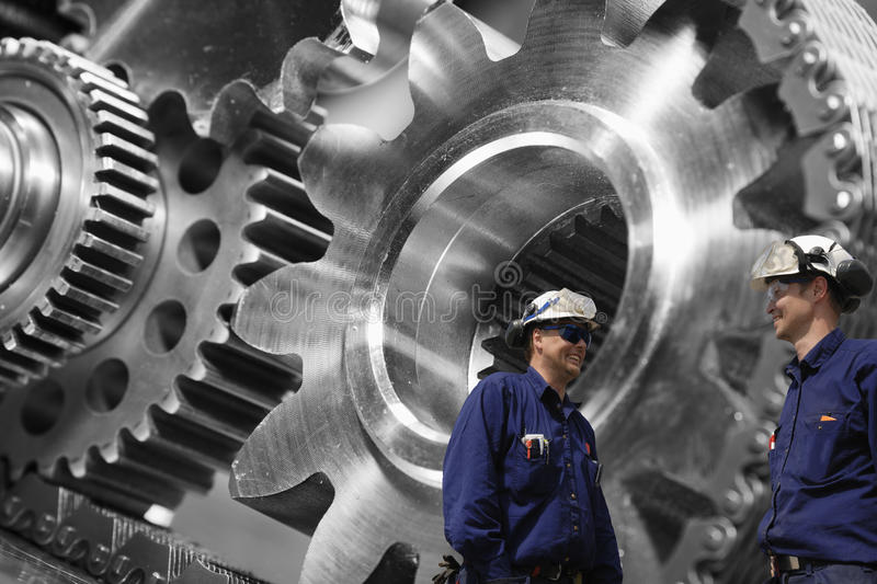 Engineers examining large gears and cog machinery. Engineers, workers talking, with large industrial titanium and steel gears in background royalty free stock image