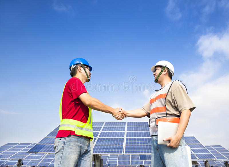 Engineers handshaking before solar power station. Two engineers handshaking before large solar power station stock photos