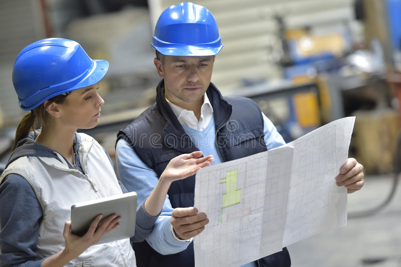Engineers in industrial factory reading instructions. Engineers in mechanical factory reading instructions stock photos