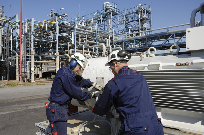 Engineers inside oil refinery. Two engineers working inside oil-refinery, industrial plant, mans face showing is released stock photography