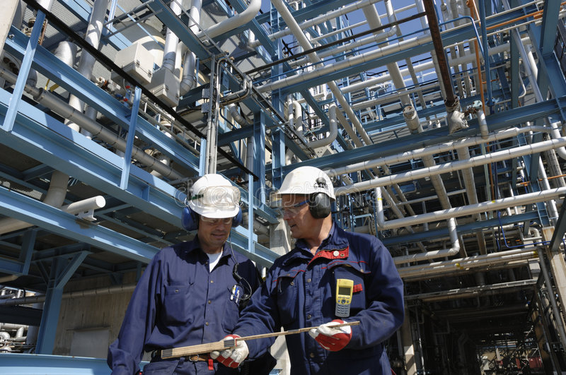 Engineers inside oil-refinery. Two engineers wearing hard-hats inside oil-refinery with lots of pipelines in the background, all trademarks removed royalty free stock image