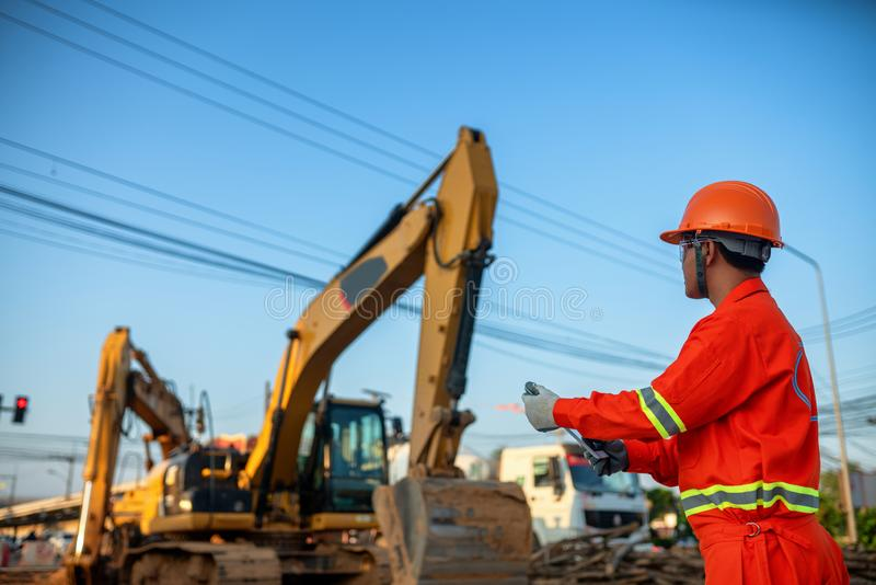 Engineers inspect the backhoe on the construction site royalty free stock photography
