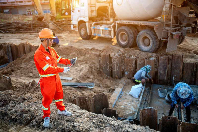 Engineers inspect the pouring of concrete stock images
