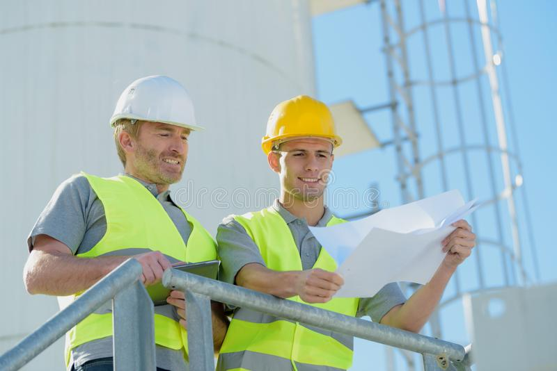 Engineers looking into factory from outside stock images