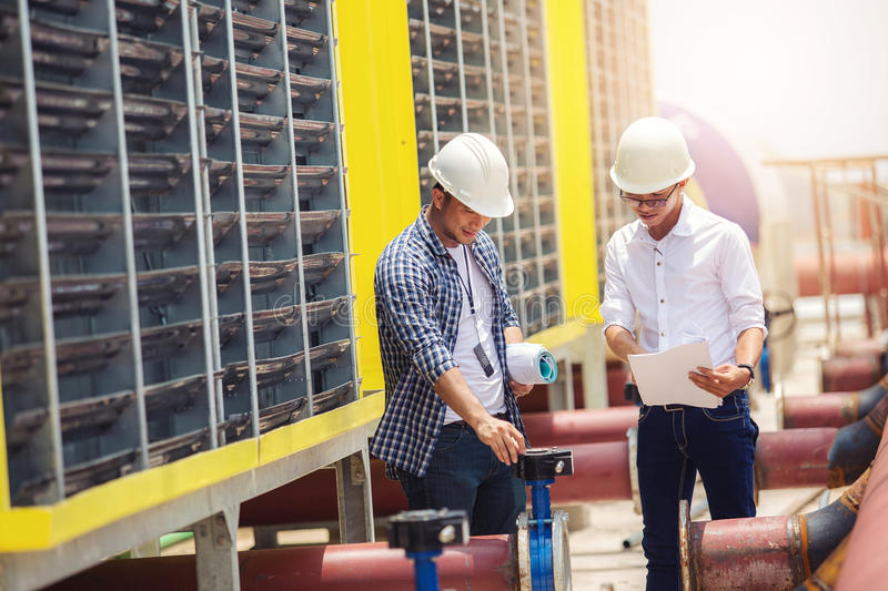 Engineers in mechanical factory reading instructions stock image