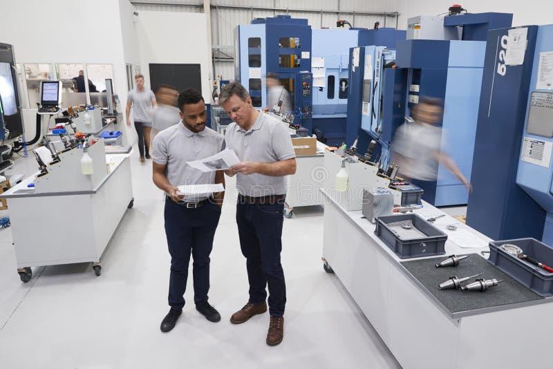 Engineers Meeting On Factory Floor Of Busy Engineering Workshop stock images