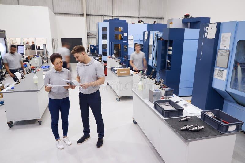 Engineers Meeting On Factory Floor Of Busy Engineering Workshop stock photos
