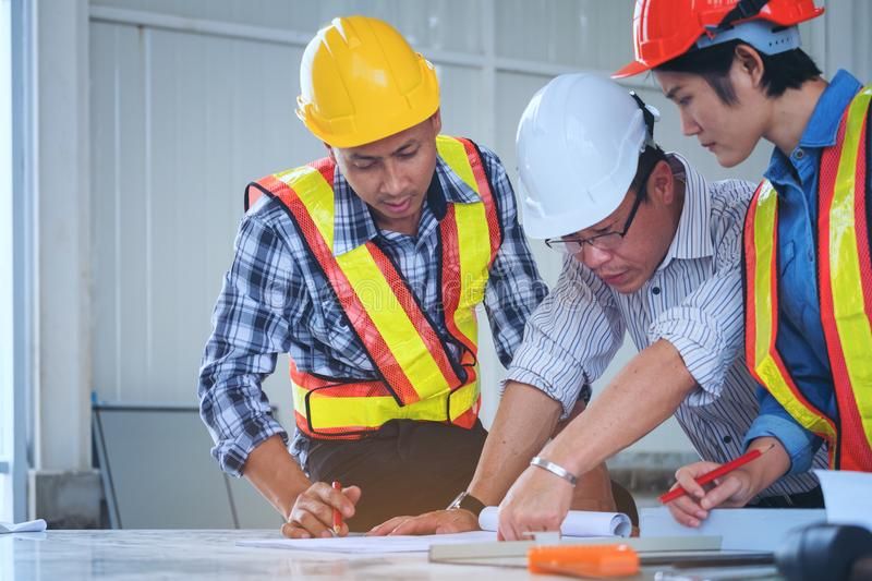 Engineers are meeting, working and looking blueprint in the office to discuss.Engineering tools and construction concept. royalty free stock photography