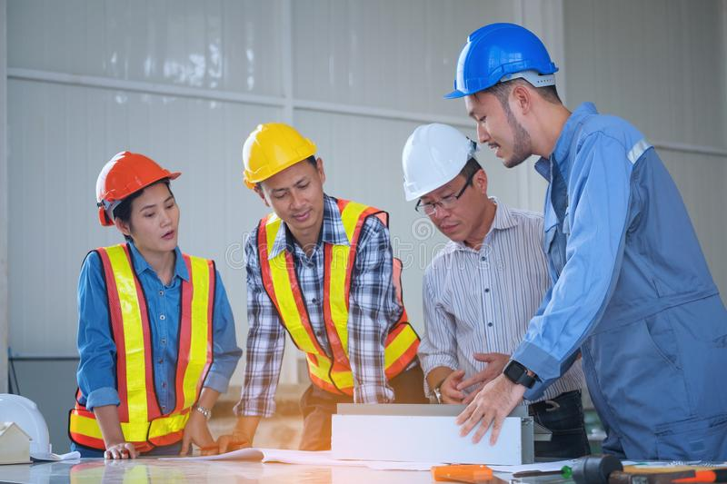 Engineers are meeting, working and looking at Home blueprint in royalty free stock image