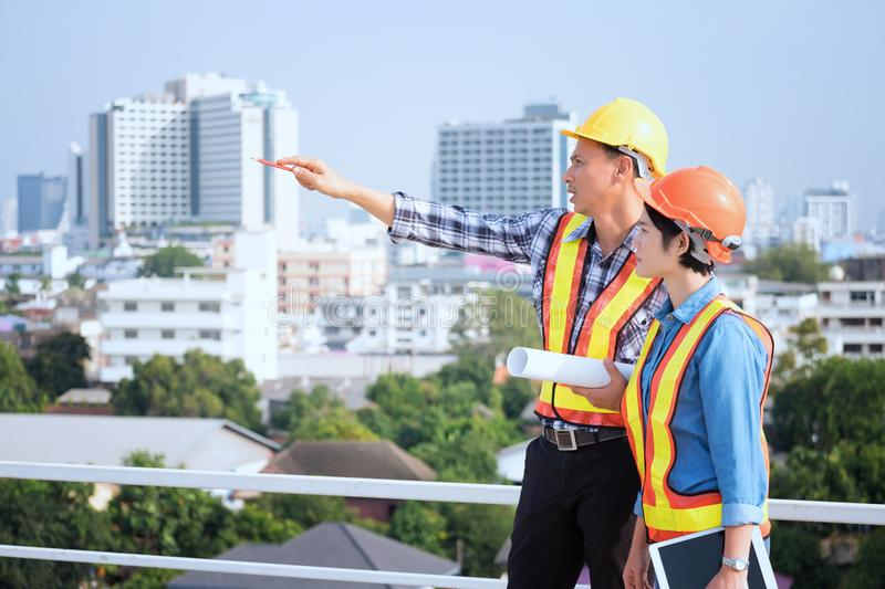 Engineers are meeting, working and looking at Home blueprint in stock photo