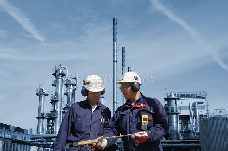 Engineers with oil and gas refinery. Engineers in hard-hat standing in front of oil and gas refinery as background, refinery in a blue toning concept stock photos