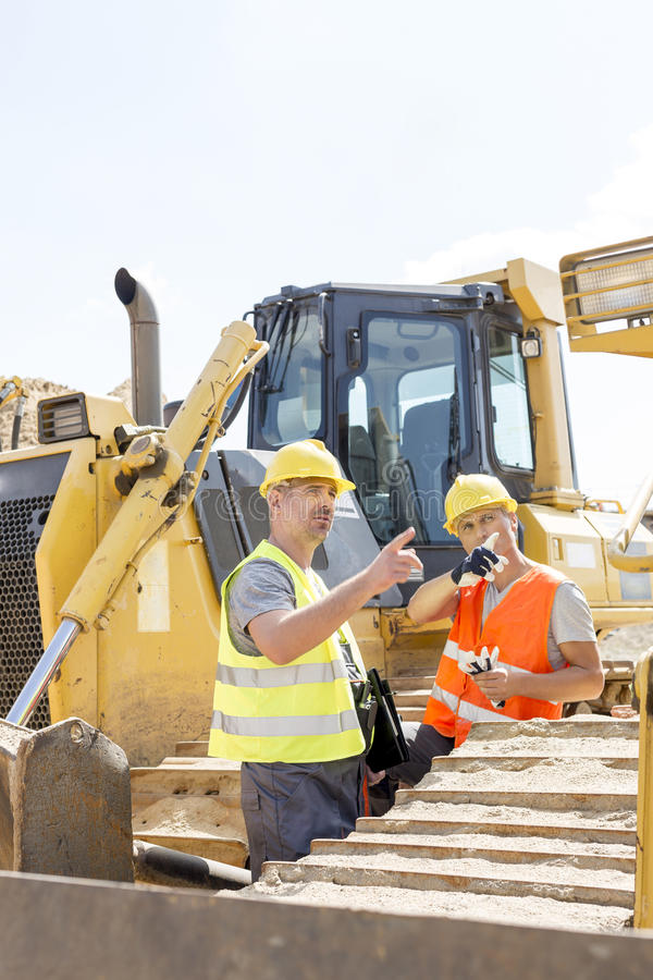 Engineers pointing while discussing at construction site against clear sky stock images