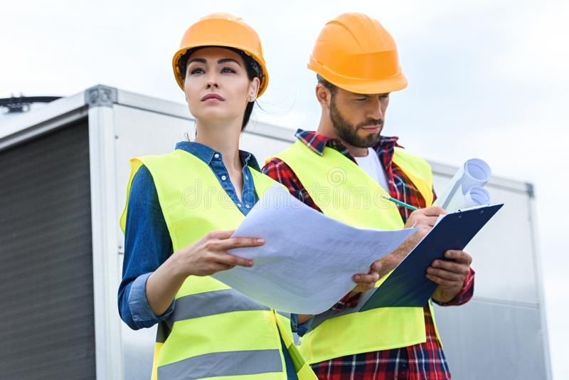 engineers in safety vests and helmets working with blueprints and clipboard on roof stock image