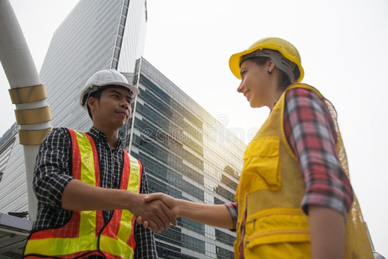 Engineerss shake hands to celebrate success day royalty free stock image