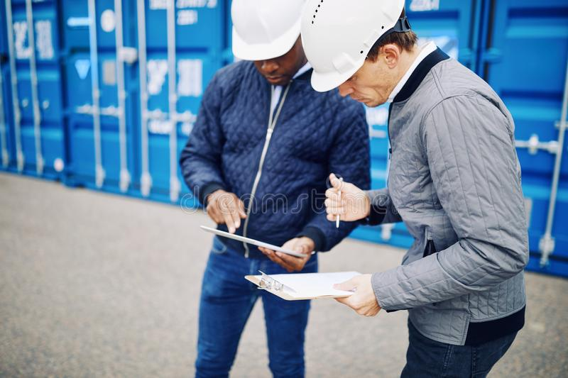 Engineers standing in a shipping yard comparing inventory lists royalty free stock images