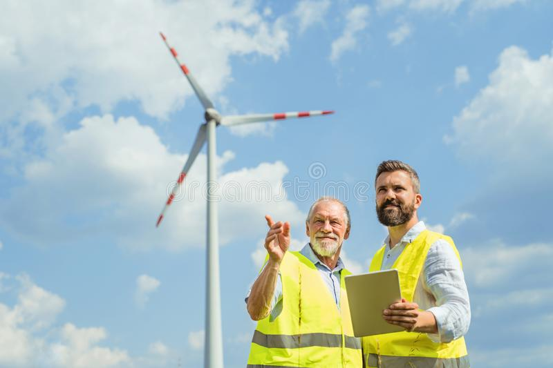 Engineers standing on wind farm, making notes. Two engineers or technicians with clipboard standing on wind farm, making notes royalty free stock photo